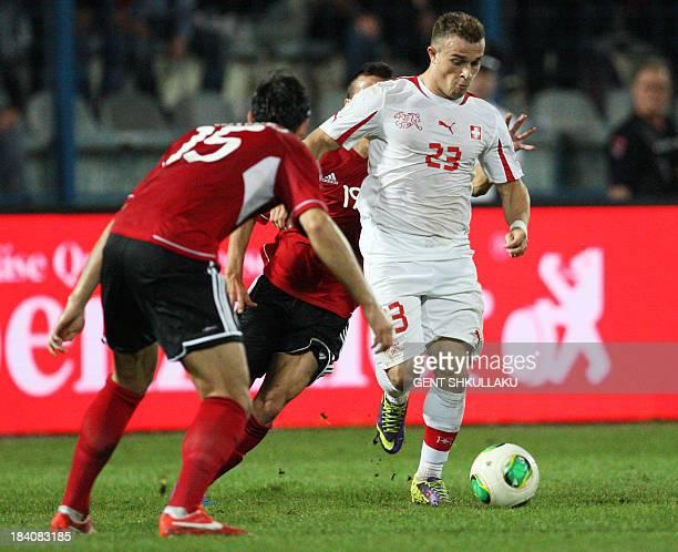 Albania's Ergys Kace and Mergim Mavraj vie for the ball with Switzerland's Xherdan Shaqiri during the FIFA 2014 World Cup qualifying football match...