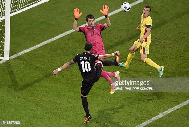 TOPSHOT Albania's forward Armando Sadiku scores the opening goal past Romania's goalkeeper Ciprian Anton Tatarusanu during the Euro 2016 group A...