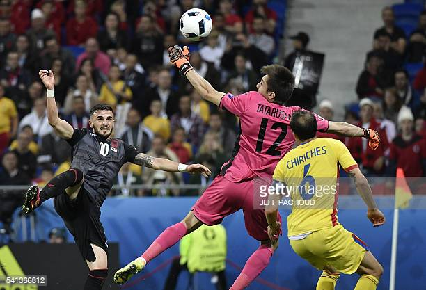 TOPSHOT Albania's forward Armando Sadiku scores the opening goal past Romania's goalkeeper Ciprian Anton Tatarusanu and Romania's defender Vlad...