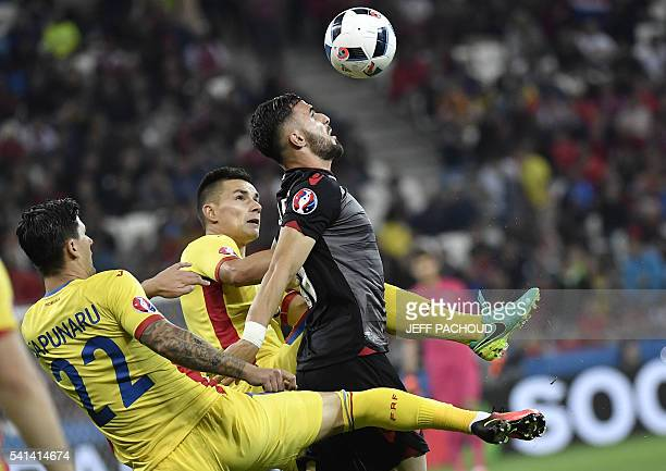 TOPSHOT Albania's forward Armando Sadiku vies for the ball with Romania's defender Cristian Sapunaru and Romania's midfielder Ovidiu Hoban during the...