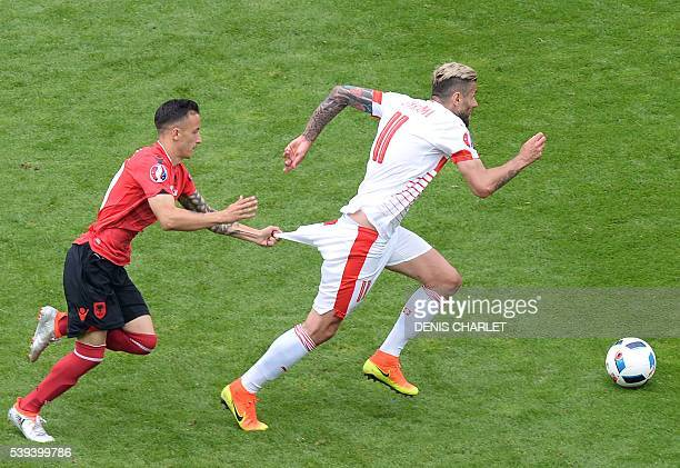 TOPSHOT Albania's midfielder Ergys Kace pulls down the shorts of Switzerland's midfielder Valon Behrami during the Euro 2016 group A football match...