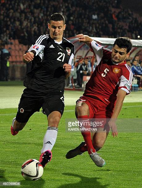 Albania's Odise Roshi vies for the ball with Armenia's Robert Arzumanyan during the Euro 2016 group I qualifying football match between Armenia and...