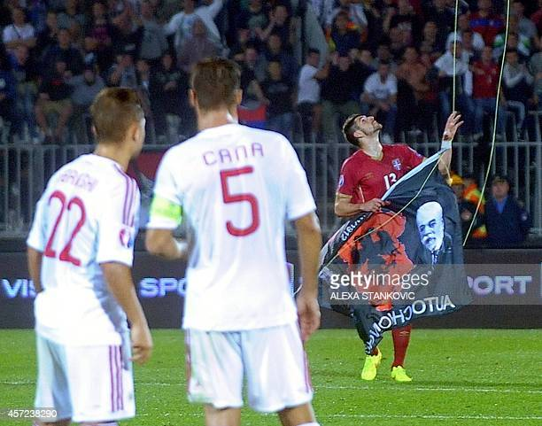 Albania's players look at Serbia's defender Stefan Mitrovic grabbing a flag with Albanian national symbols from remotely operated drone flown over...