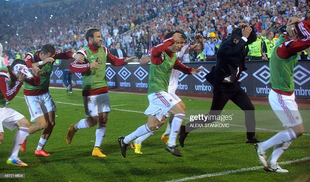 Albania's players run for cover during the EURO 2016 group I football match between Serbia and Albania in Belgrade on October 14 2014 AFP PHOTO /...