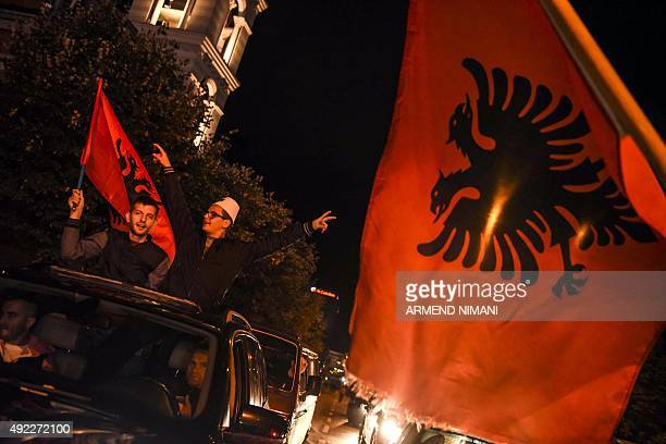 Albania's supporters celebrate the victory and the qualification of their team at the end of the Euro 2016 group I qualifying football match between...