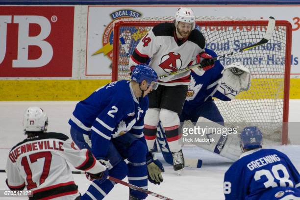 Albany Devils left wing Brian Gibbons screens Albany Devils center John Quenneville shot as it finds the net through Toronto Marlies defenseman...