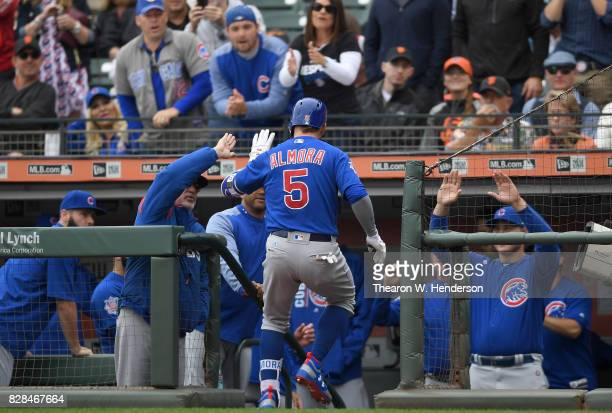 Albert Almora Jr #5 of the Chicago Cubs is congratulated by manager Joe Maddon and teammates after Almora Jr hit a solo home run against the San...