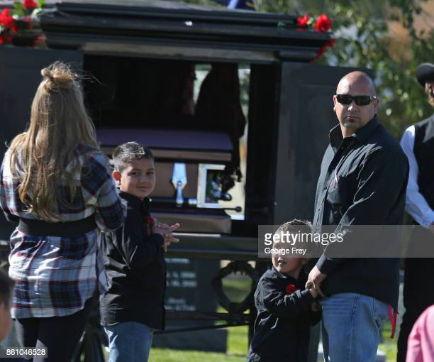 Albert Alvarado the husband of Heather Lorraine Alvarado and their children wait for the casket to be removed from a horse drawn hurst at the...