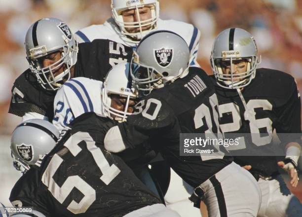 Albert Bentley Running Back for the Indianapolis Colts is tackled by Stacey Toran Jerry Robinson and Jerry Robinson for the Los Angeles Raiders...