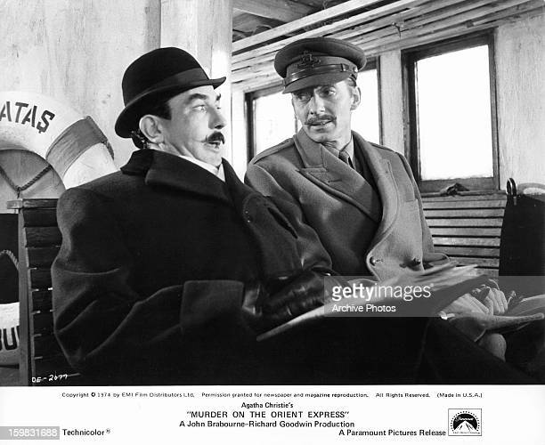 Albert Finney sits next to a man in a scene from the film 'Murder On The Orient Express' 1974