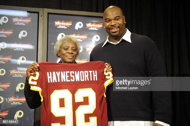 Albert Haynesworth and his mom Linda pose with his team jersey at a press conference after signing a 7year contract worth approximately $100 million...