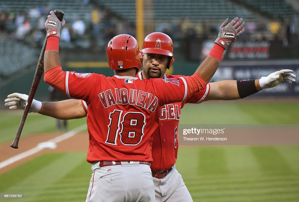 Albert Pujols #5 and Luis Valbuena #18 of the Los Angeles Angels of Anaheim celebrates after Pujols hit a solo home run against the Oakland Athletics in the top of the first inning at Oakland Alameda Coliseum on May 9, 2017 in Oakland, California.