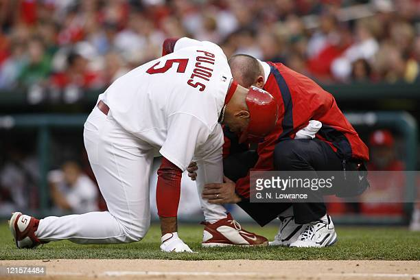 Albert Pujols has his calf tended too after fouling a ball off during action between the New York Mets and the St Louis Cardinals at Busch Stadium in...