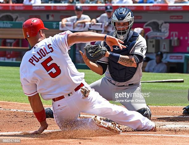 Albert Pujols of the Los Angeles Angels beats the tag of Gary Sanchez of the New York Yankees to score in the first inning of the game at Angel...