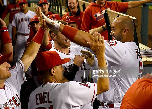 Albert Pujols of the Los Angeles Angels is greeted in the dugout after a solo home run in the first inning of the game against the Cincinnati Reds at...