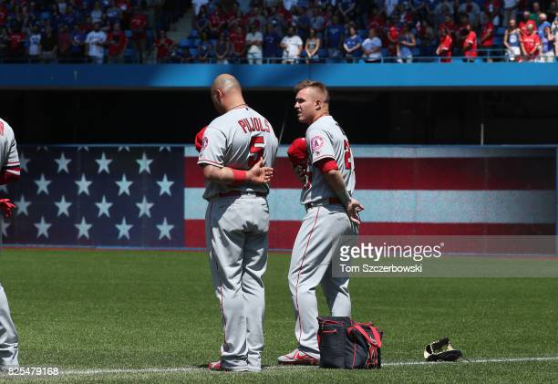 Albert Pujols of the Los Angeles Angels of Anaheim and Mike Trout stand for the playing of the American anthem as an American flag is displayed on...