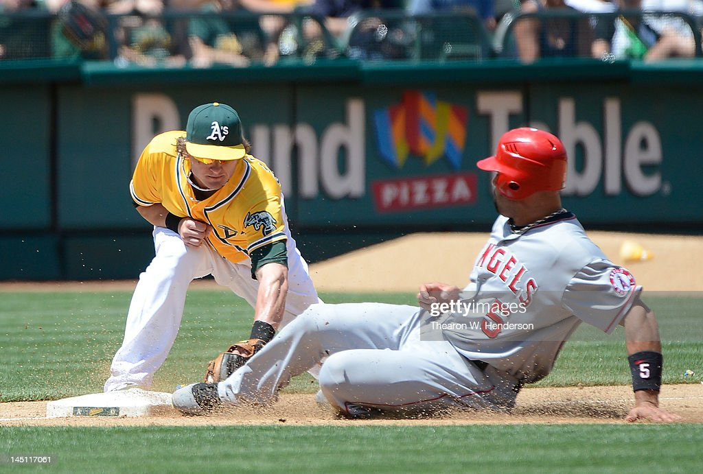 <a gi-track='captionPersonalityLinkClicked' href=/galleries/search?phrase=Albert+Pujols&family=editorial&specificpeople=171151 ng-click='$event.stopPropagation()'>Albert Pujols</a> #5 of the Los Angeles Angels of Anaheim attempting to go from first to third on a single to center is thrown out, tagged by Josh Donaldson #20 of the Oakland Athletics in the six inning at O.co Coliseum on May 23, 2012 in Oakland, California.