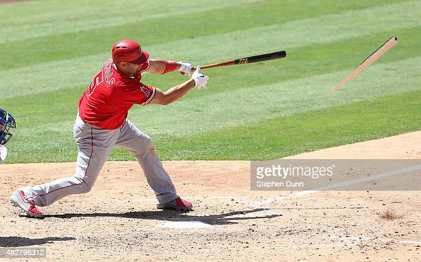 Albert Pujols of the Los Angeles Angels of Anaheim breaks his bat and grounds out but brings in a run from third base in the sixth inning against the...