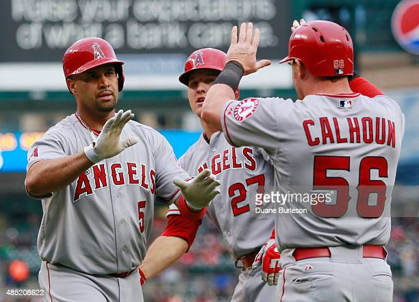 Albert Pujols of the Los Angeles Angels of Anaheim celebrates his threerun home run against the Detroit Tigers with Mike Trout and Kole Calhoun...