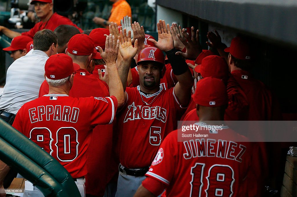 <a gi-track='captionPersonalityLinkClicked' href=/galleries/search?phrase=Albert+Pujols&family=editorial&specificpeople=171151 ng-click='$event.stopPropagation()'>Albert Pujols</a> #5 (C) of the Los Angeles Angels of Anaheim celebrates in the dugout after Mark Trumbo hit a three run home run against the Houston Astros in the first inning at Minute Maid Park on May 7, 2013 in Houston, Texas.