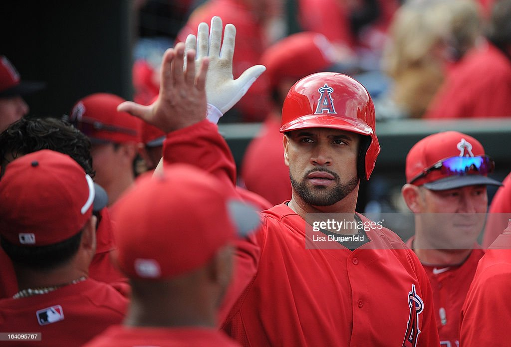 <a gi-track='captionPersonalityLinkClicked' href=/galleries/search?phrase=Albert+Pujols&family=editorial&specificpeople=171151 ng-click='$event.stopPropagation()'>Albert Pujols</a> #5 of the Los Angeles Angels of Anaheim celebrates with his teammates after hitting a home run against the Colorado Rockies at Tempe Diablo Stadium on March 9, 2013 in Peoria, Arizona.