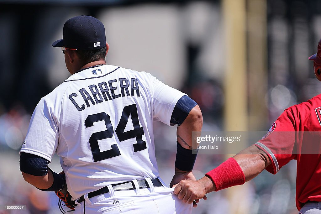 Albert Pujols #5 of the Los Angeles Angels of Anaheim gives a tug on the belt loop of Miguel Cabrera #24 of the Detroit Tigers while on first base during the fourth inning of the game at Comerica Park on April 19, 2014 in Detroit, Michigan. The Tigers defeated the Angels 5-2.