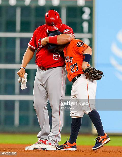 Albert Pujols of the Los Angeles Angels of Anaheim gives Jose Altuve of the Houston Astros a headlock after doubling in the fourth inning at Minute...