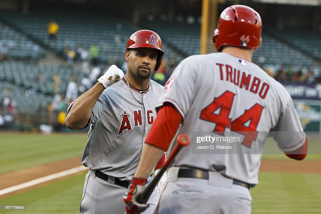 Albert Pujols #5 of the Los Angeles Angels of Anaheim is congratulated by Mark Trumbo #44 after hitting a home run against the Oakland Athletics during the first inning at O.co Coliseum on April 29, 2013 in Oakland, California.