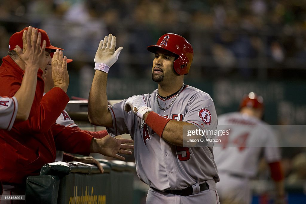 Albert Pujols #5 of the Los Angeles Angels of Anaheim is congratulated by teammates in the dugout after hitting a home run against the Oakland Athletics during the seventh inning at O.co Coliseum on April 29, 2013 in Oakland, California. The Oakland Athletics defeated the Los Angeles Angels of Anaheim 10-8 in 19 innings.
