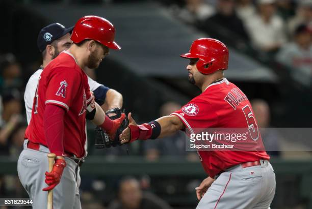 Albert Pujols of the Los Angeles Angels of Anaheim is greeted by CJ Cron of the Los Angeles Angels of Anaheim after scoring a run during a game...