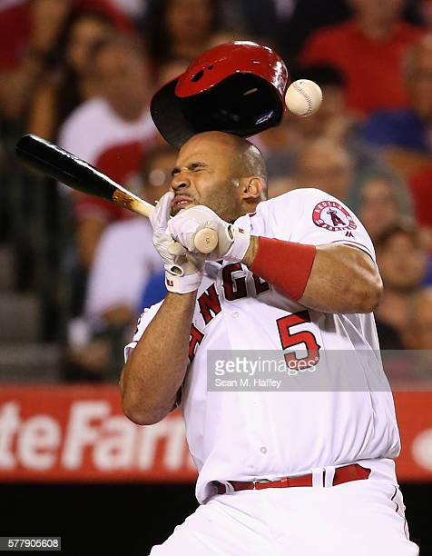 Albert Pujols of the Los Angeles Angels of Anaheim reacts to being hit in the head by a pitch from Tony Barnette of the Texas Rangers during the...