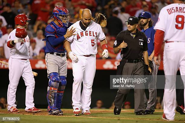 Albert Pujols of the Los Angeles Angels of Anaheim reacts to being hit in the head by a pitch from Tony Barnette as Robinson Chirinos of the Texas...