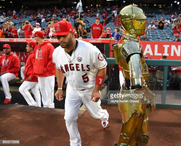 Albert Pujols of the Los Angeles Angels of Anaheim runs on the the field past C3PO on Star Wars promotional night before the game against the Texas...