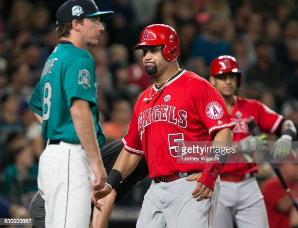 Albert Pujols of the Los Angeles Angels of Anaheim scores on a double by Andrelton Simmons as pitcher Andrew Moore of the Seattle Mariners looks on...