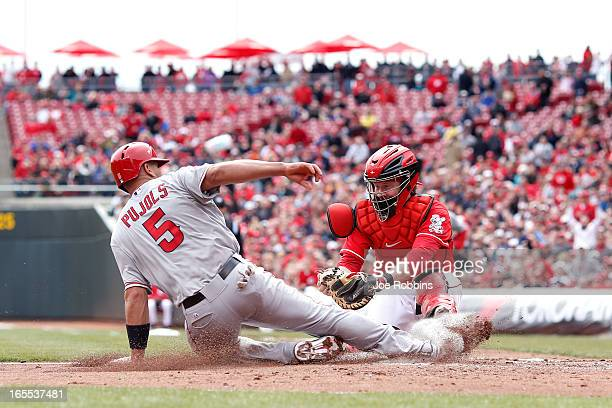 Albert Pujols of the Los Angeles Angels of Anaheim slides into home ahead of the tag by Ryan Hanigan of the Cincinnati Reds during the third inning...