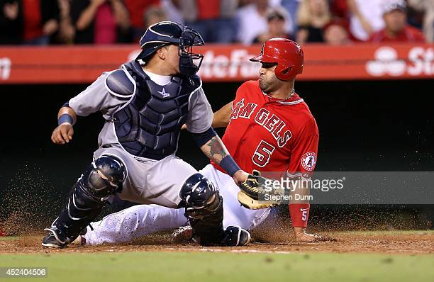 Albert Pujols of the Los Angeles Angels of Anaheim slides past catcher Jesus Sucre of the Seattle Mariners to score a run to tie the score at 11 at...