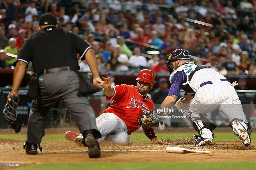 Albert Pujols of the Los Angeles Angels slides in safely to score past the tag from catcher Jarrod Saltalamacchia of the Arizona Diamondbacks during...