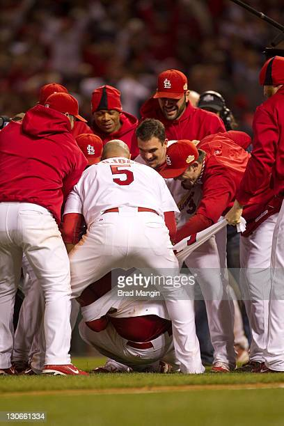 Albert Pujols of the St Louis Cardinals and teammates tear the jersey off of David Freese after his walkoff home run in the 11th inning of Game Six...