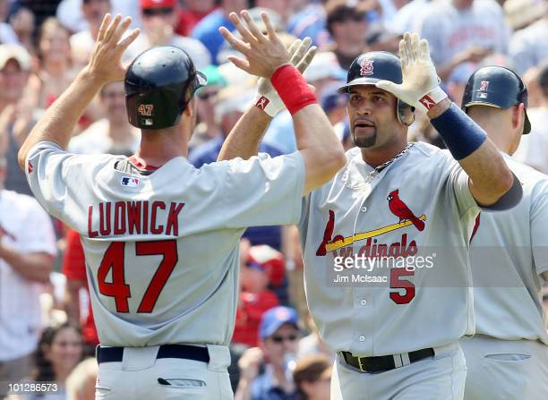 Albert Pujols of the St Louis Cardinals celebrates his fifth inning two run home run against the Chicago Cubs with teammate Ryan Ludwick on May 30...