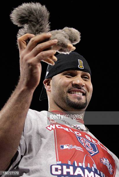 Albert Pujols of the St Louis Cardinals celebrates with a toy rally squirrel after defeating the Texas Rangers 62 to win Game Seven of the MLB World...