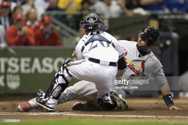 Albert Pujols of the St Louis Cardinals is tagged out trying to score against Jonathan Lucroy of the Milwaukee Brewers in the top of the first inning...