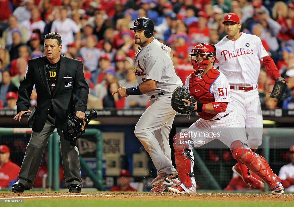 Albert Pujols of the St Louis Cardinals scores the fourth run in the top of the eleventh inning against Carlos Ruiz of the Philadelphia Phillies with...