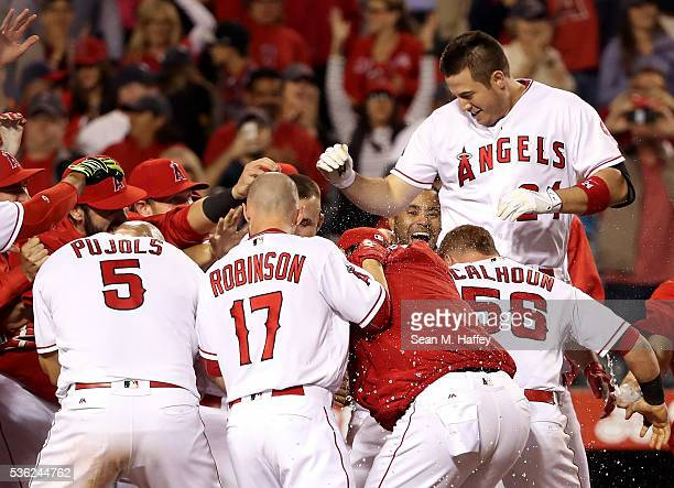 Albert Pujols Shane Robinson and Kole Calhoun of the Los Angeles Angels of Anaheim swarm CJ Cron of the Los Angeles Angels of Anaheim after Cron hit...