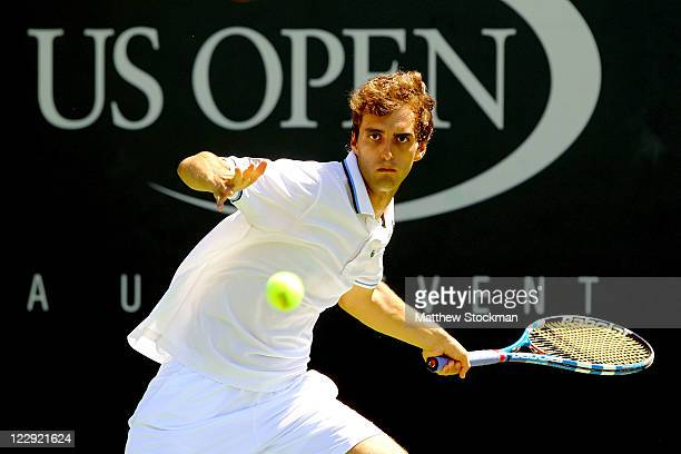 Albert Ramos of Spain returns the ball against Philipp Petzschnerof Germany during Day One of the 2011 US Open at the USTA Billie Jean King National...