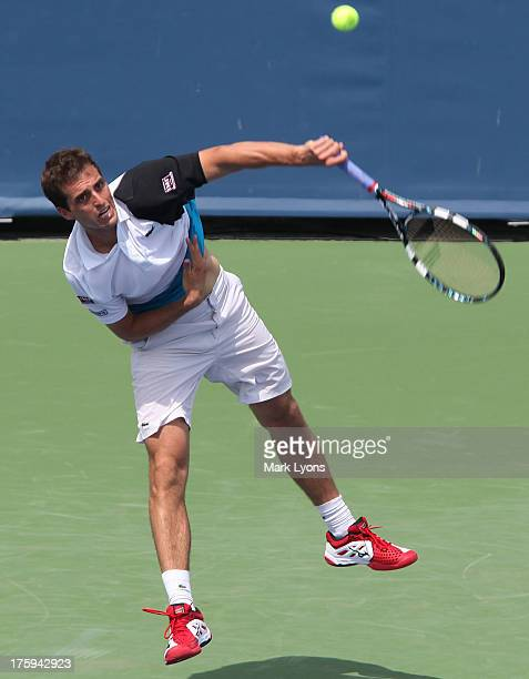 Albert Ramos of Spain serves to Tim Smyczek of the United States during the qualifying round of the Western and Southern Open at the Lindner Family...