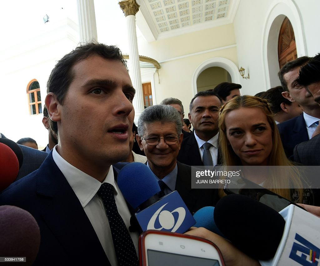 Albert Rivera (L), candidate for prime minister of Spain for the Ciudadanos party on a visit to Venezuela to support the opposition, next to National Assembly President Henry Ramos Allup (C), Lilian Tintori (R), wife of jailed Venezuelan opposition leader Leopoldo Lopez, outside the legislature in Caracas on May 24, 2016. / AFP / JUAN
