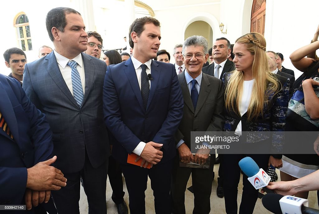 Albert Rivera (2nd-L), candidate for prime minister of Spain for the Ciudadanos party on a visit to Venezuela to support the opposition, next to National Assembly President Henry Ramos Allup (2nd-R), Lilian Tintori (R), wife of jailed Venezuelan opposition leader Leopoldo Lopez, outside the legislature in Caracas on May 24, 2016. / AFP / JUAN