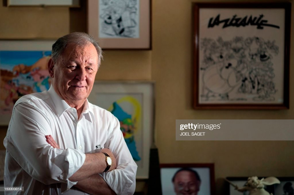 Albert Uderzo, French author and illustrator who launched the Asterix comics strip character in 1959 with author Rene Goscinny, who appears on a picture at the bottom, poses in front of a drawing tittled 'La Zizanie' in his office on October 2, 2012 in Neuilly-sur-Seine, outside Paris. Uderzo will release an comic strip book entitled 'L'integrale' on October 11, 2012, under the artistic direction of photographer Philippe Cauvin and Alain Duchene.
