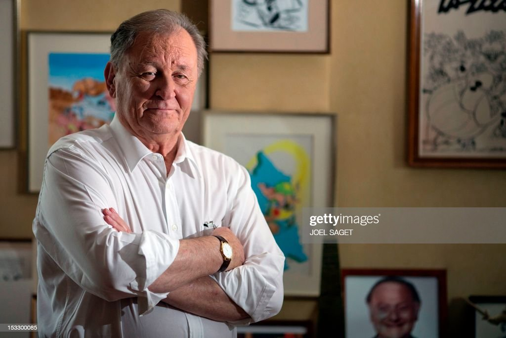 Albert Uderzo, French author and illustrator who launched the Asterix comics strip character in 1959 with author Rene Goscinny, who appears on a picture in the bottom, poses in his office at his home on October 2, 2012 in Neuilly-sur-Seine, outside Paris. Uderzo will release an comic strip book entitled 'L'integrale' on October 11, 2012, under the artistic direction of photographer Philippe Cauvin and Alain Duchene.