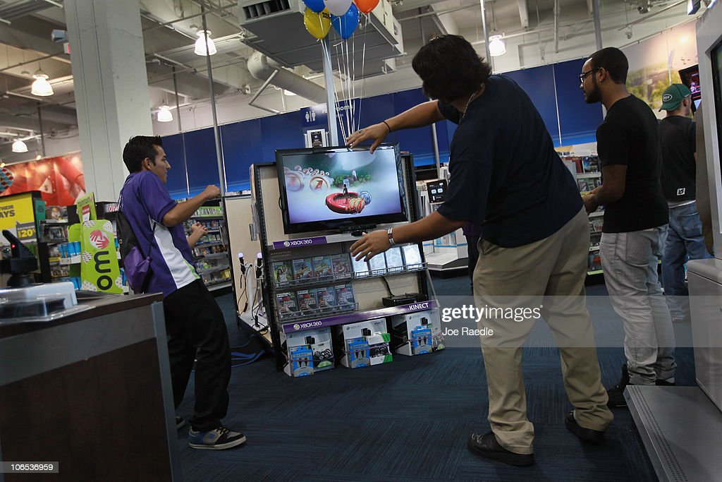 Albert Ulloa (C) plays a game with Microsoft's new Kinect controller for the Xbox 360 as the Xbox representative Charles Leano (L) looks on at the Best Buy store on November 4, 2010 in Miami Beach, Florida. The Kinect went on sale today and uses sensors to read the players body language so controllers are not necessary to play Xbox games with the Kinect.